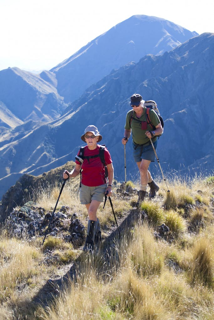 Marie and Bob top out after sweating up a steep tussock spur