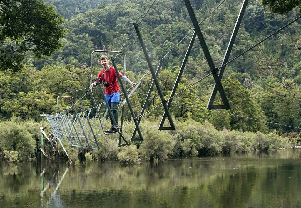 Malcolm tiptoes along the three ­wire bridge over the swollen Seaforth River. Photo: Ray Salisbury
