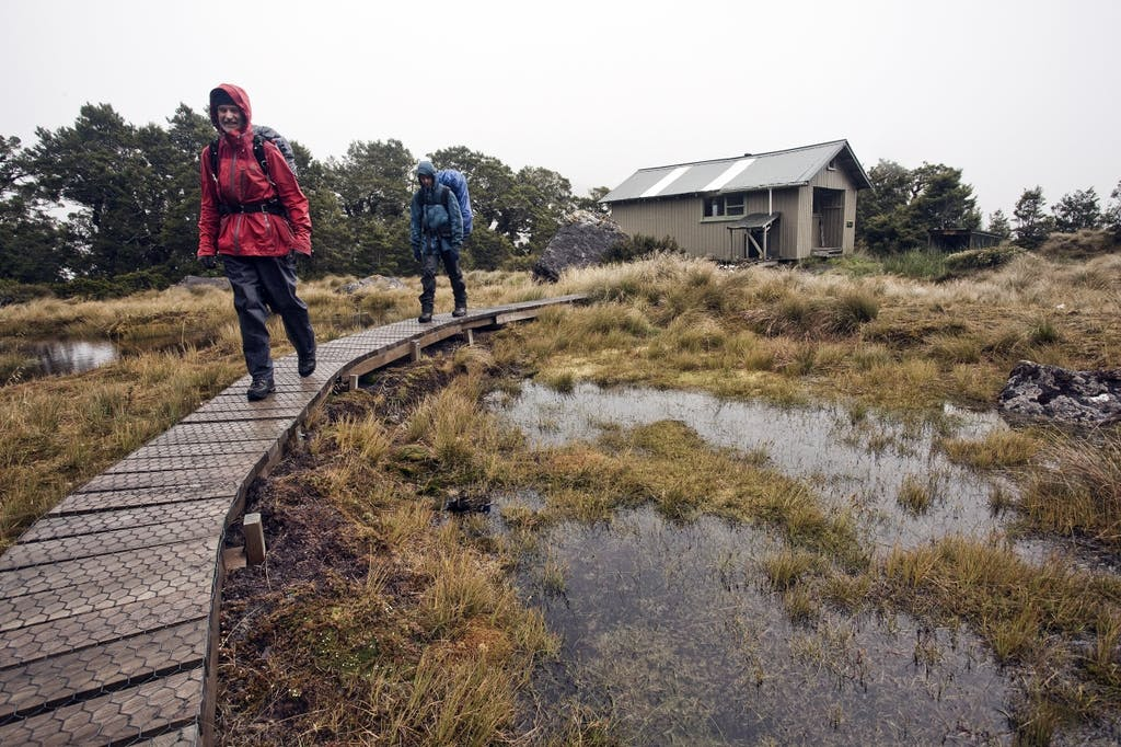 Trampers depart Lake Roe Hut for drier and warmer climes. Photo: Ray Salisbury