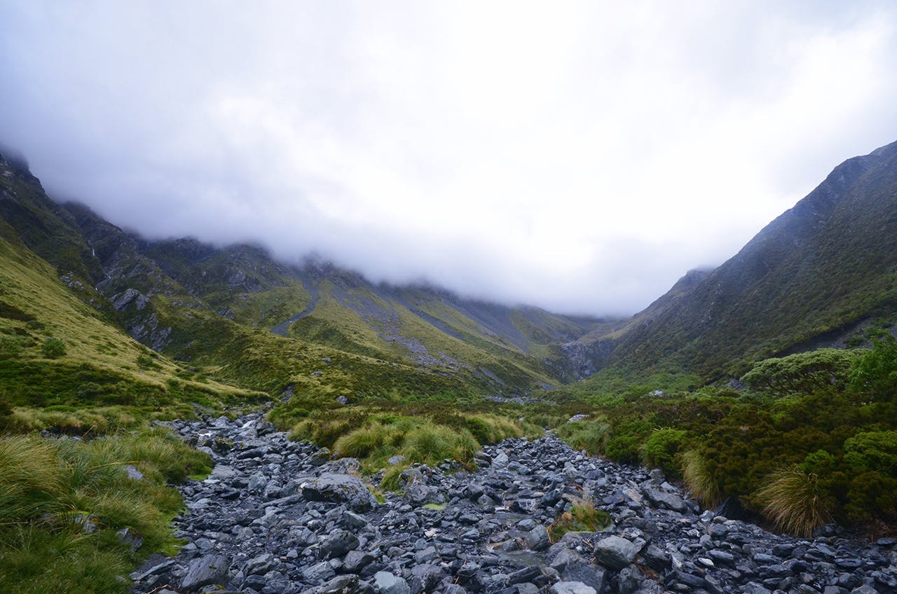Dark and menacing clouds, heavy with rain, gather at the head of the Arahura Valley. Photo: Ricky French