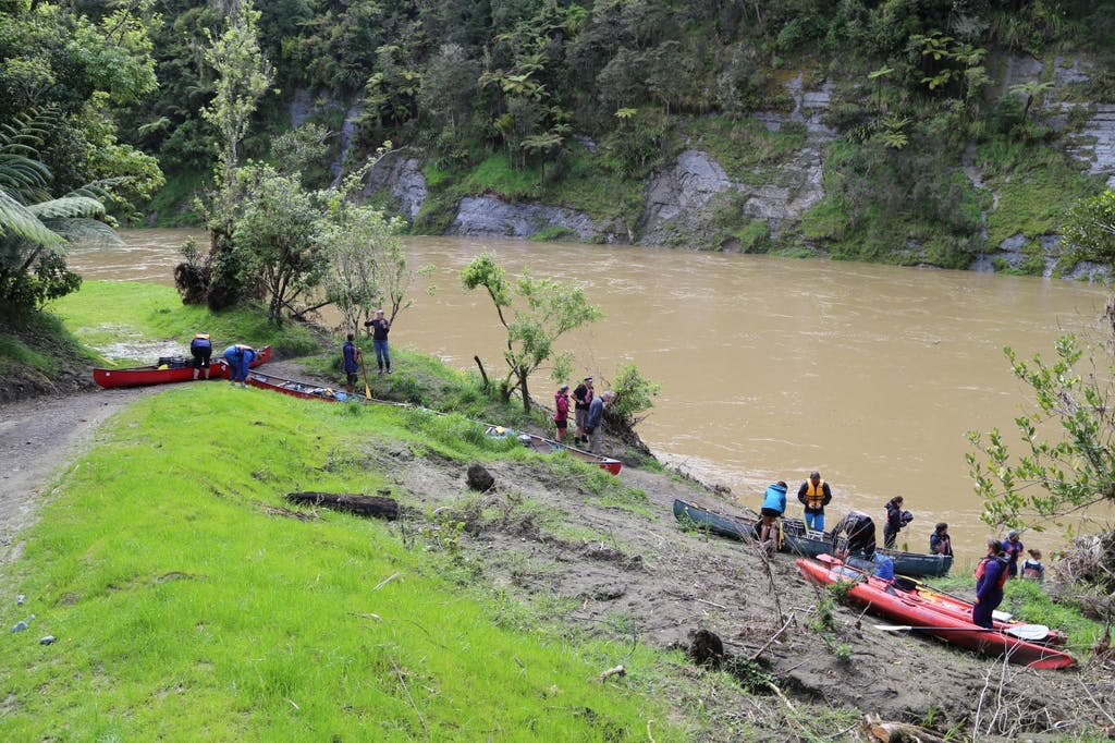 Kayakers prepare for take-off into a high river from John Coull Hut .Photo: Matthew Pike