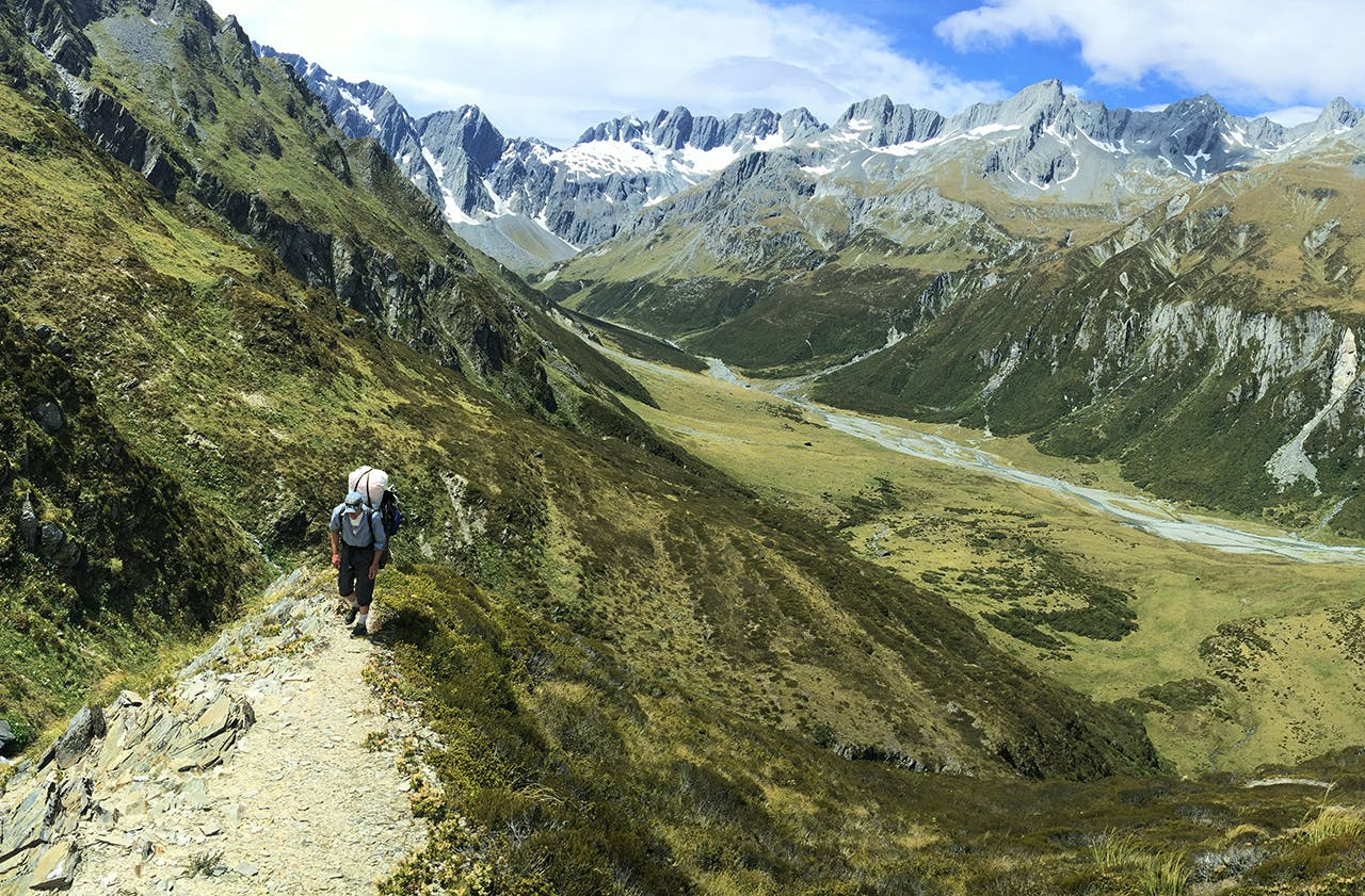 A packrafter carries his boat over Brodrick Pass. Photo: Thor Tingey