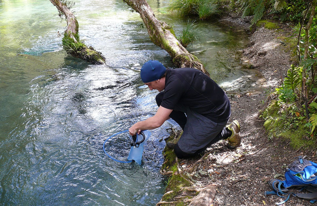 The author collects water from an area above the mills, where it is still safe to drink. Photo: Josh Gale