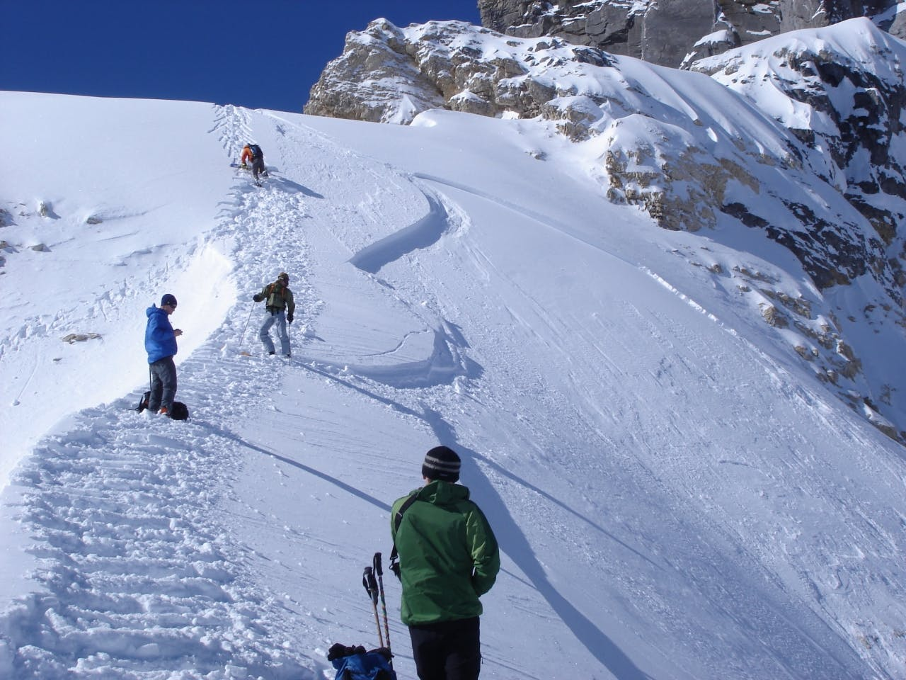 Backcountry skiers climb a safe ridge next to a slope which has just avalanched – if in doubt about the route, speak up
