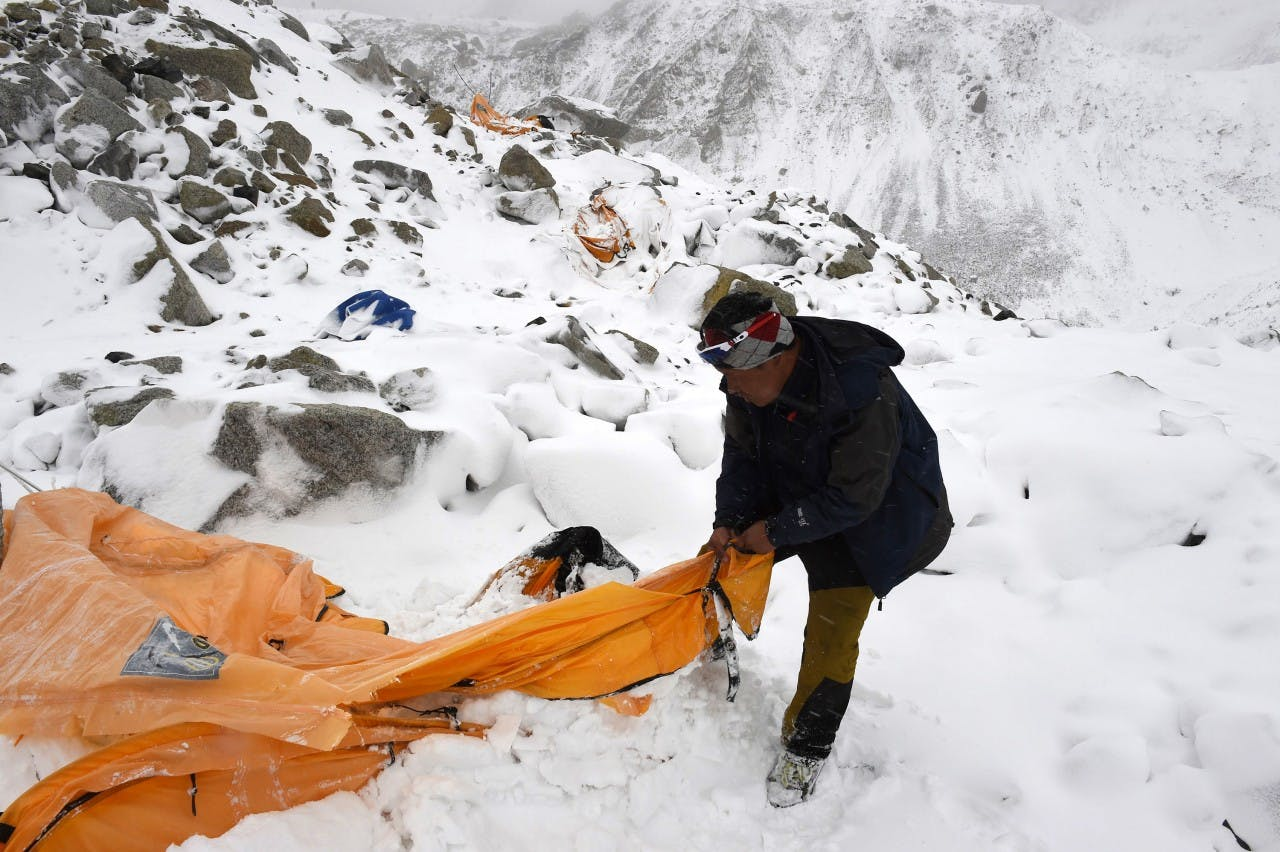 Trekking guide Pasang Sherpa searches for survivors among flattened tents moments after the avalanche at Everest Base Camp. PHOTO: Roberto Schmidt