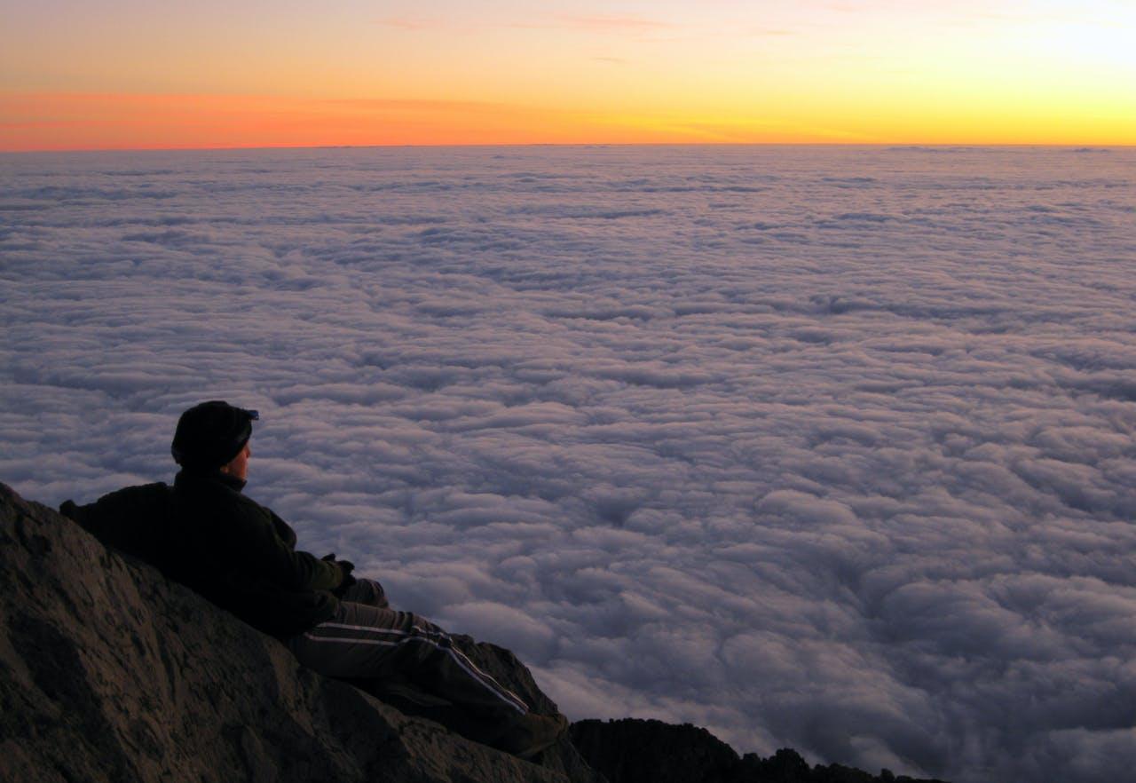 Jamie Bai enjoys a spectacular sunset before bivying the night on Mt Taranaki, in Egmont National Park. Photo: Marcus Bai