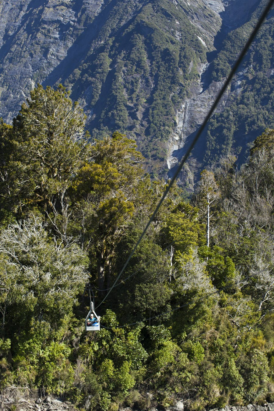 Hana Black crosses the cableway over the Karangarua River to access Regina Creek and the track to Conical Hill. Photo: Mark Watson