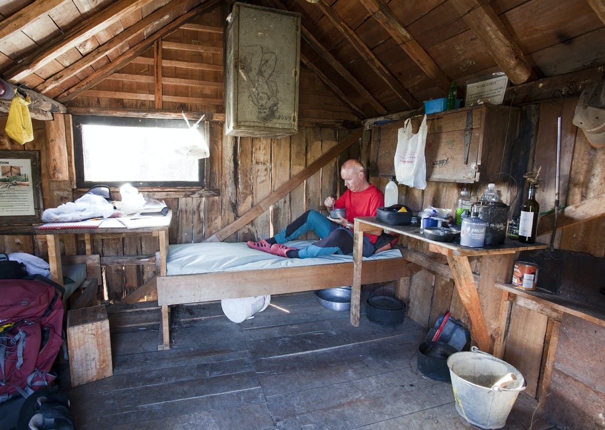 A tramper soaks in the atmosphere of the restored Riordans Hut – the first on the track to get an upgrade. Photo: Ray Salisbury