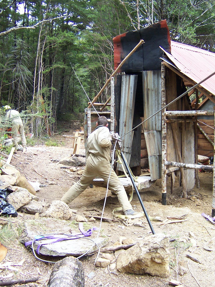 Rebuilding the hearth at Waingaro Forks hut required some heavy lifting. Photo: John Taylor