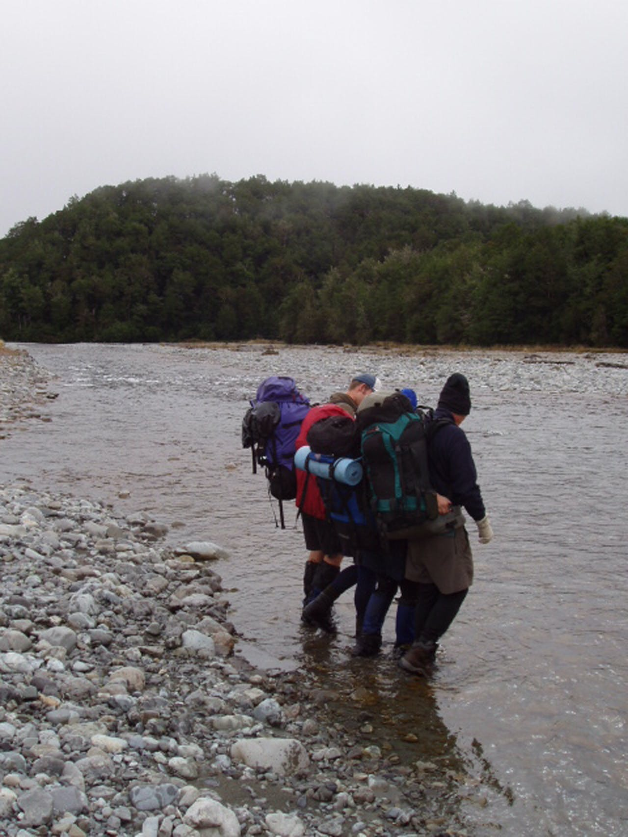 Trampers demonstrate the mutual support method for crossing rivers