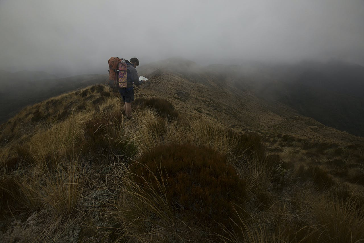 Navigating in low cloud on the tops above the Moonlight Track. One of the concerns voiced about the route is inexperienced hikers will need to travel through long exposed sections with little shelter. Photo: Neil Silverwood