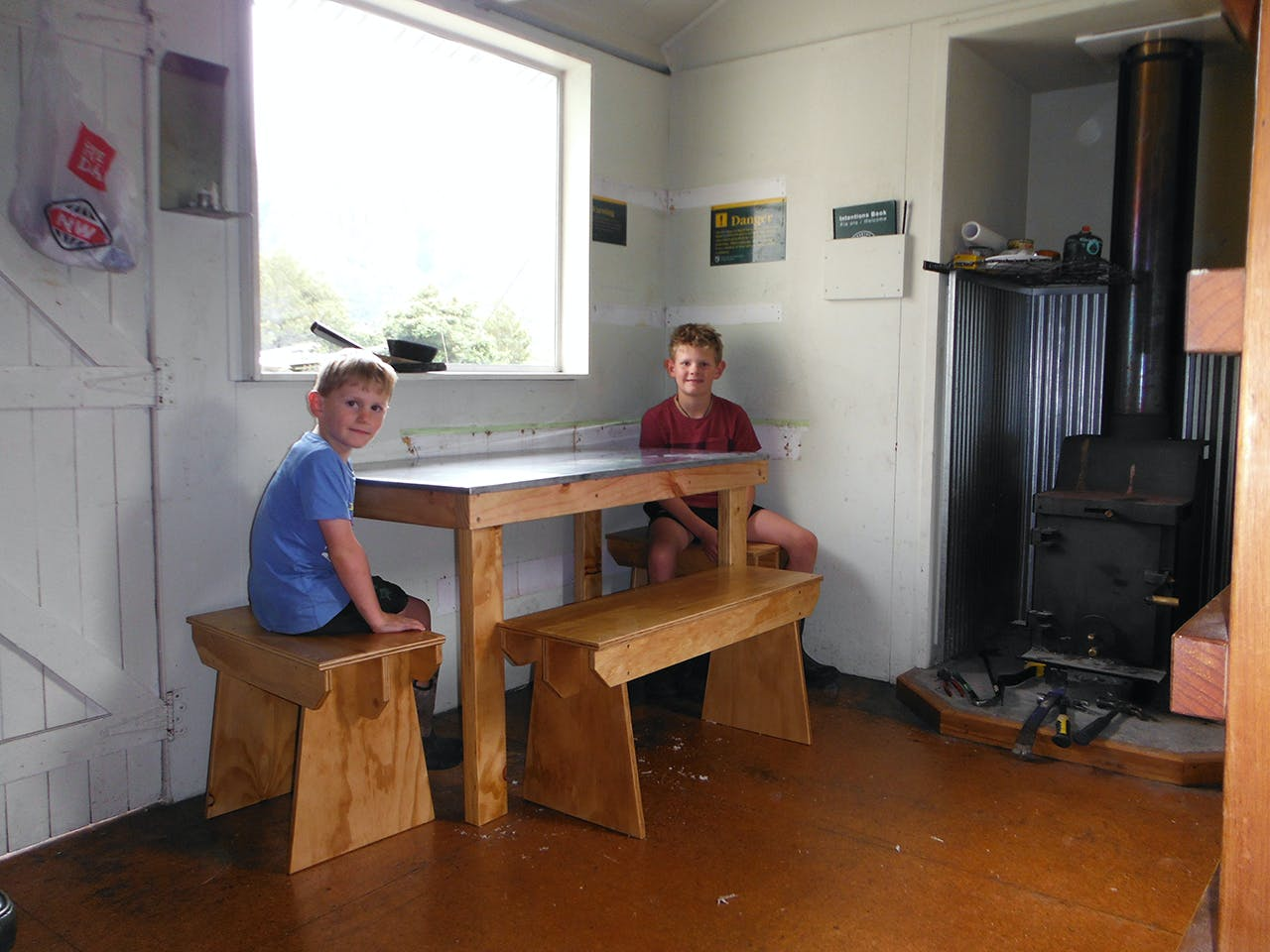 Enjoying the fruits of their labour - a seat at the hut's new bench. Photo: Supplied