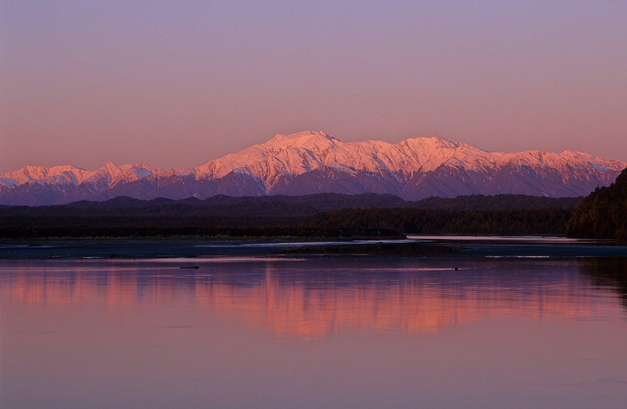 The Southern Alps tower over a mirror-calm Okarito Lagoon. Photo: Steve Baker/Black Robin Photography