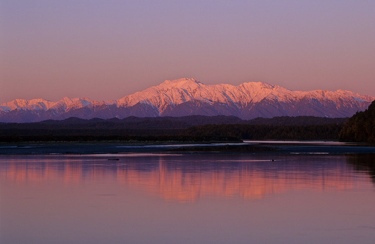 The Southern Alps tower over a mirror-calm Okarito Lagoon. Photo: Steve Baker/Black Robin Photography
